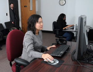 Dr. Hong Sheng, foreground, reviews eye-tracking heat maps in the Laboratory for Information Technology Evaluation at Missouri S&T. In the background are business and information technology student Sneha Pochinapeddi (seated) and Dr. Nick Lockwood. Sheng and Lockwood are assistant professors of business and information technology at Missouri S&T.