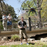 Chris Seto controls the multicopter while Dr. Zhaozheng Yin (far left) and Yunxiang Mao observe.