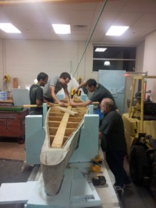 Students work on the canoe, while being observed by Bob Phelan, outreach manager of the student design center.