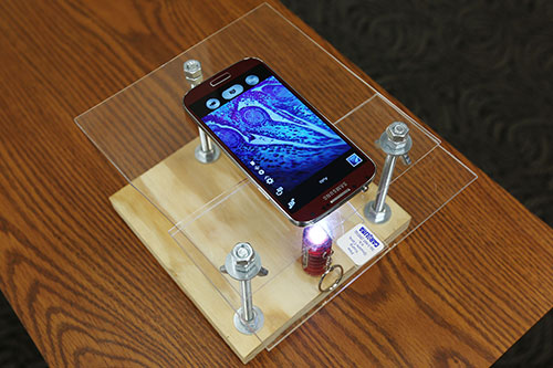 Daniel Miller, a recent biological sciences M.S. graduate, built this do-it-yourself microscope with a smartphone and less than $10 in materials. (Photo by Sam O'Keefe.)