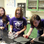From left: Hannah Kim, Kelsey Crossen and Katherine Nelson prepare to conduct a gel electrophoresis. Photo by Kira Buckowing.
