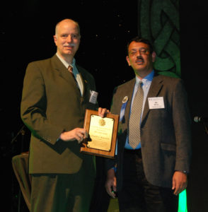 Don Wunsch, left, accepts the International Neural Networks Society's Gabor Award from INNS president Ali Minai during an awards ceremony in Dublin.
