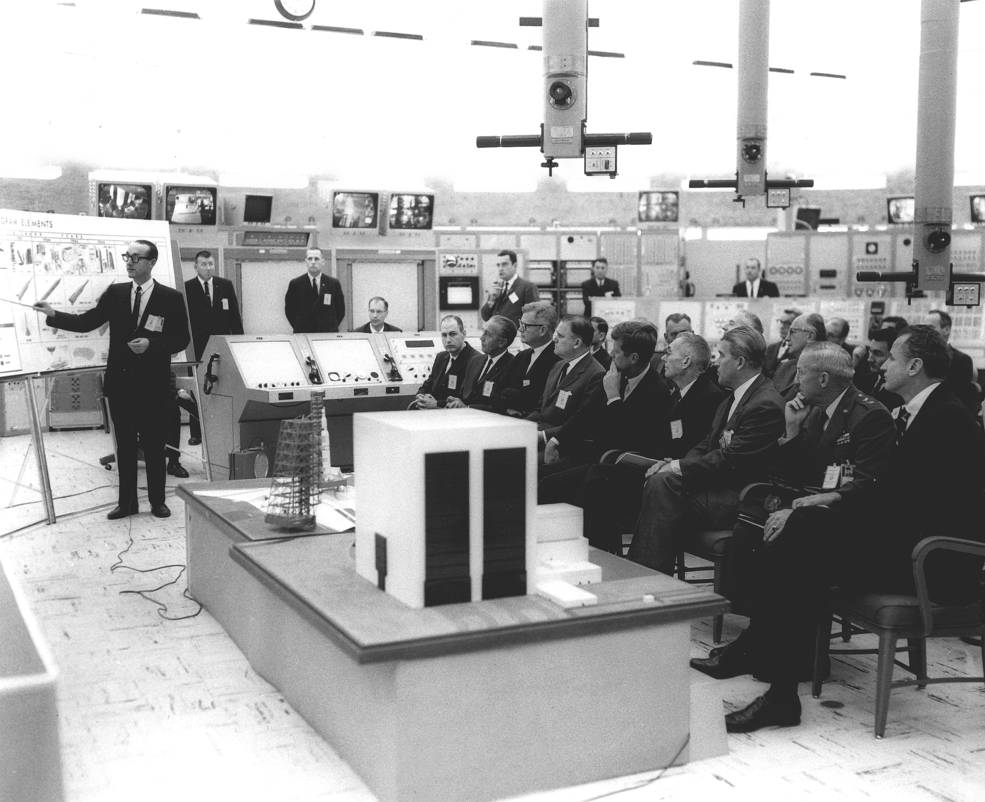 Dr. George Mueller briefs President John F. Kennedy and other officials on the Saturn V rocket. Front row, left to right: George Low, Kurt Debus, Robert Seamans, James Webb, President Kennedy, Hugh Dryden, Wernher von Braun, Gen.l Leighton Davis and Senator George Smathers. Photo credit: NASA