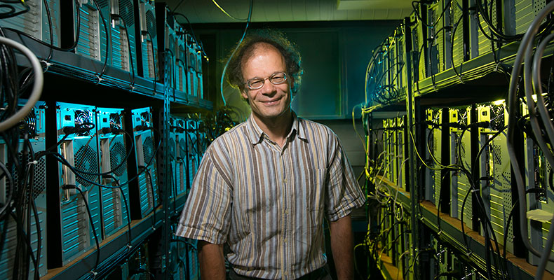 Thomas Vojta, professor of physics, poses with the Pegasus IV High-Performance Computing Cluster, a supercomputer he built with his colleagues and students to model quantum phase transitions and to compute various materials' properties. Sam O'Keefe/Missouri S&T