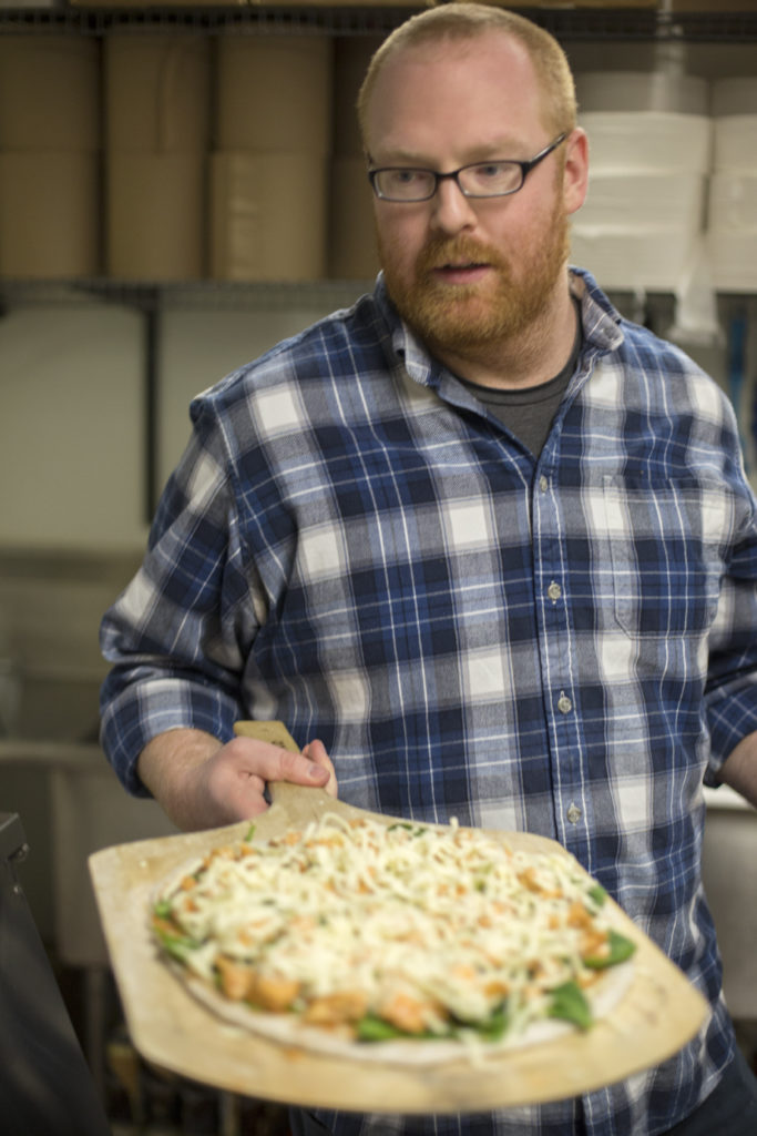 Alumnus Jon Leek puts a pizza pie into an oven at Orbit Pinball Lounge. His company, Pulse Pizza serves pizzas made with spent beer grains out of the Maplewood, Missouri, bar on Monday and Thursday nights.