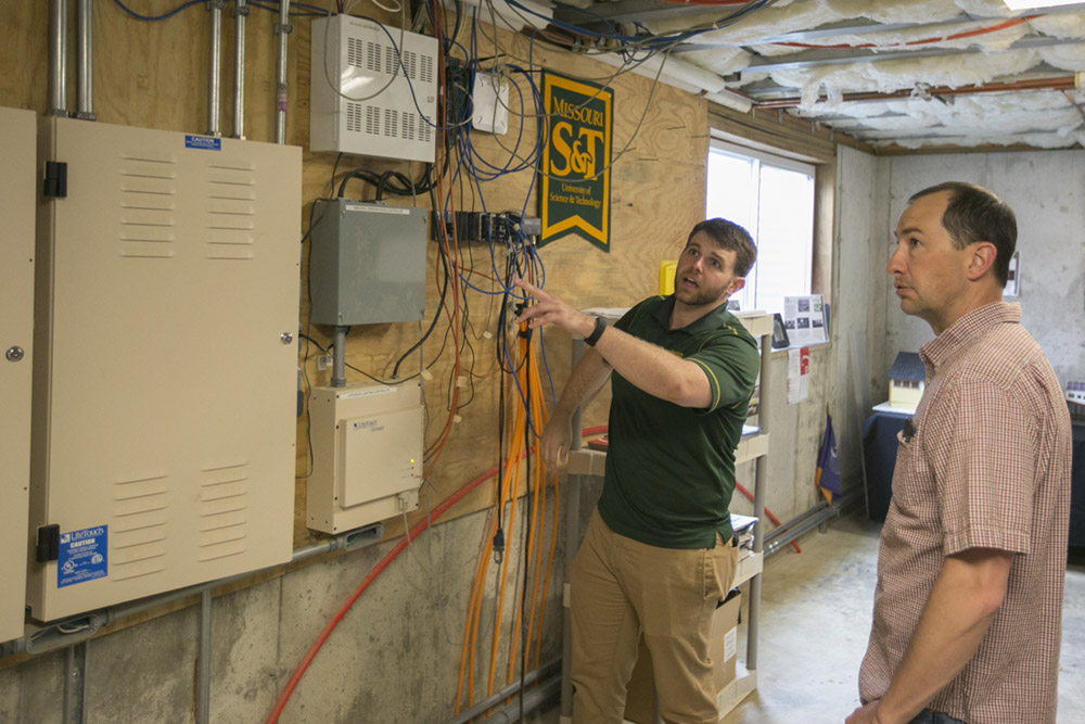 Missouri S&T doctoral student Cory Brennan, left, and Tony Anthony, assistant director of S&T's Office of Sustainable Energy and Environmental Engagement (OSE3), discuss the wiring at the Solar Village Microgrid on Tuesday, April 19, 2016.