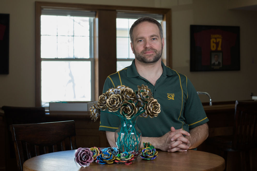 Nathan Rues, a 2002 mechanical engineering graduate, poses with some bottle cap roses he made. Rues sells the roses through his Kaps For Kids business, with part of the proceeds benefiting children's charities.