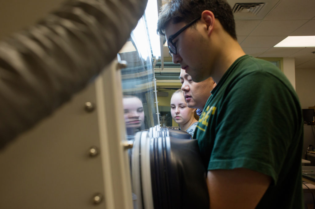Dr. Jonghyun Park oversees high school students Daniel Yoon and Jessica Slavick during the Summer Research Academy as they work in a glove box in Toomey Hall. Photo by Sam O'Keefe/Missouri S&T