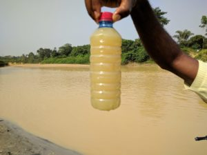 A member of Kenneth Bansah's research team holds a bottle of dirty water taken from the polluted Tano River. Kenneth Bansah.