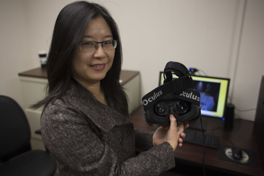 Dr. Fiona Nah, professor of business and information technology, poses with an Oculus Rift virtual reality headset in the Laboratory for Information Technology Evaluation.