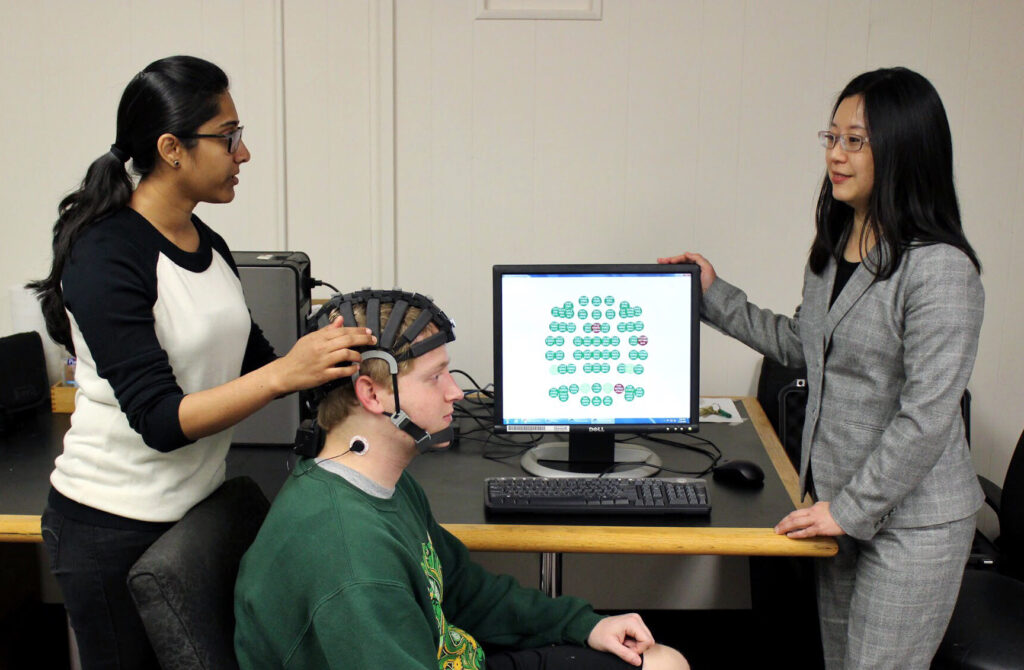 "Tejaswini Yelamanchili affixes an electroencephalogram (EEG) headset on S&T student Bryan Fox. Fox, a senior in information science and technology, is aiding Yelmanchili's research on ""flow"" by playing the video game Tetris. With Yelmanchili and Fox is Yelmanchili's advisor, Dr. Fiona Nah."