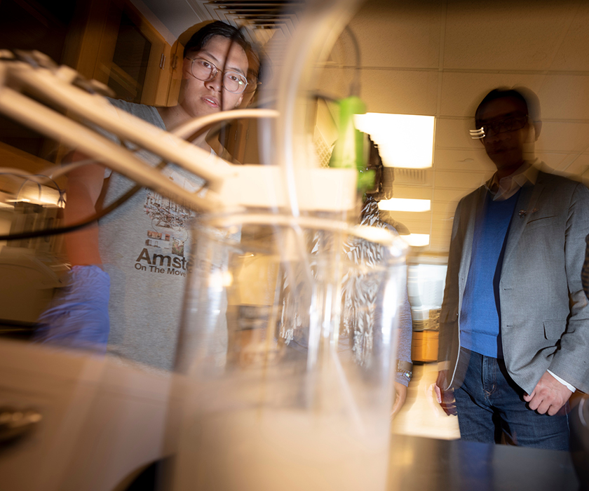 Bowen Tan, a graduate research assistant in civil engineering, adds carbon dioxide to a lime water solution as part of a nanoparticle research project led by Dr. Hongyan Ma (in background), assistant professor of civil engineering. Photo by Tom Wagner/Missouri S&T ©2019 Missouri S&T