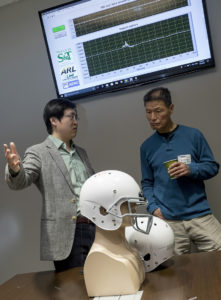 Dr. Jie Huang, assistant professor of electrical and computer engineering at Missouri S&T, demonstrates helmets he's made with fiber optic sensors to Dr Chiming Huang, associate professor of biological sciences at the University of Missouri-Kansas City, during a recent traumatic brain injury research conclave at the Army base in Fort Leonard Wood, Missouri. Photo by Tom Wagner/Missouri S&T, ©2019 Missouri S&T