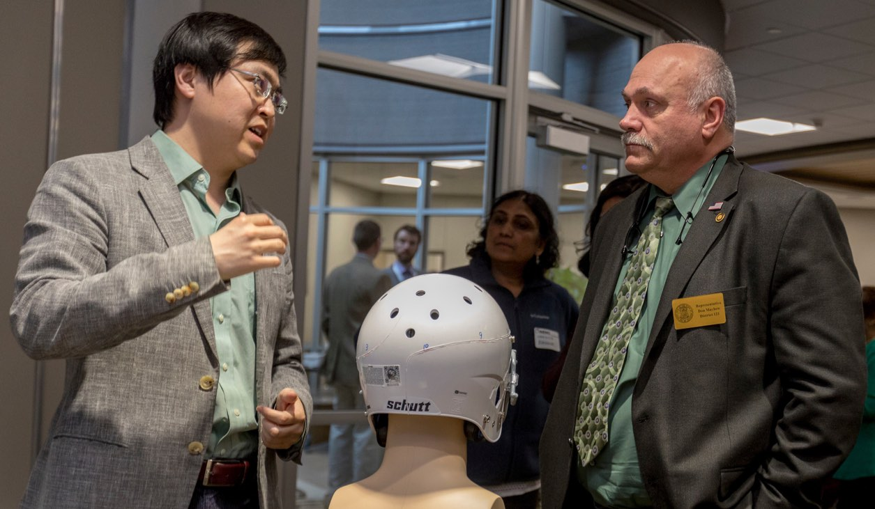 "Dr. Jie Huang (left) discusses one of his ""smart"" helmet prototypes with Missouri State Rep. Don Mayhew. Photo by Tom Wagner, Missouri S&T."