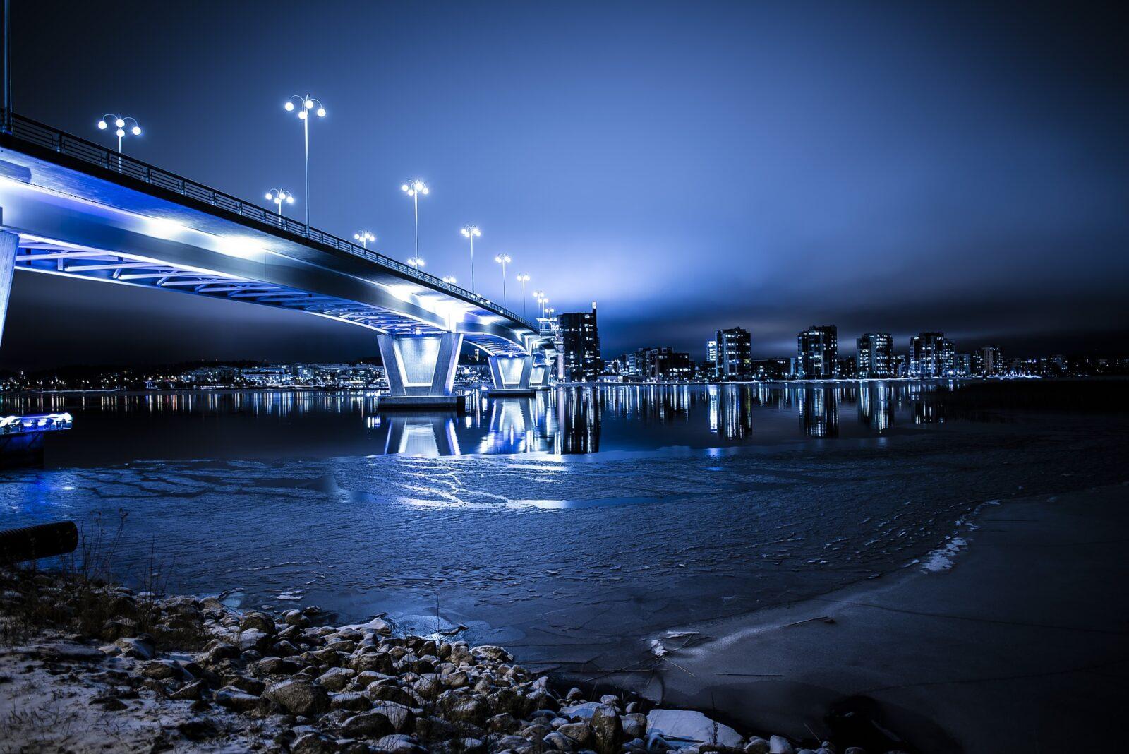 photo of bridge and city skyline at night