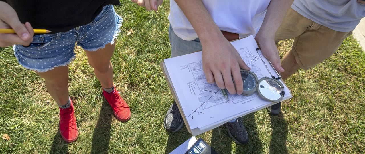 Students using a compass during class on campus