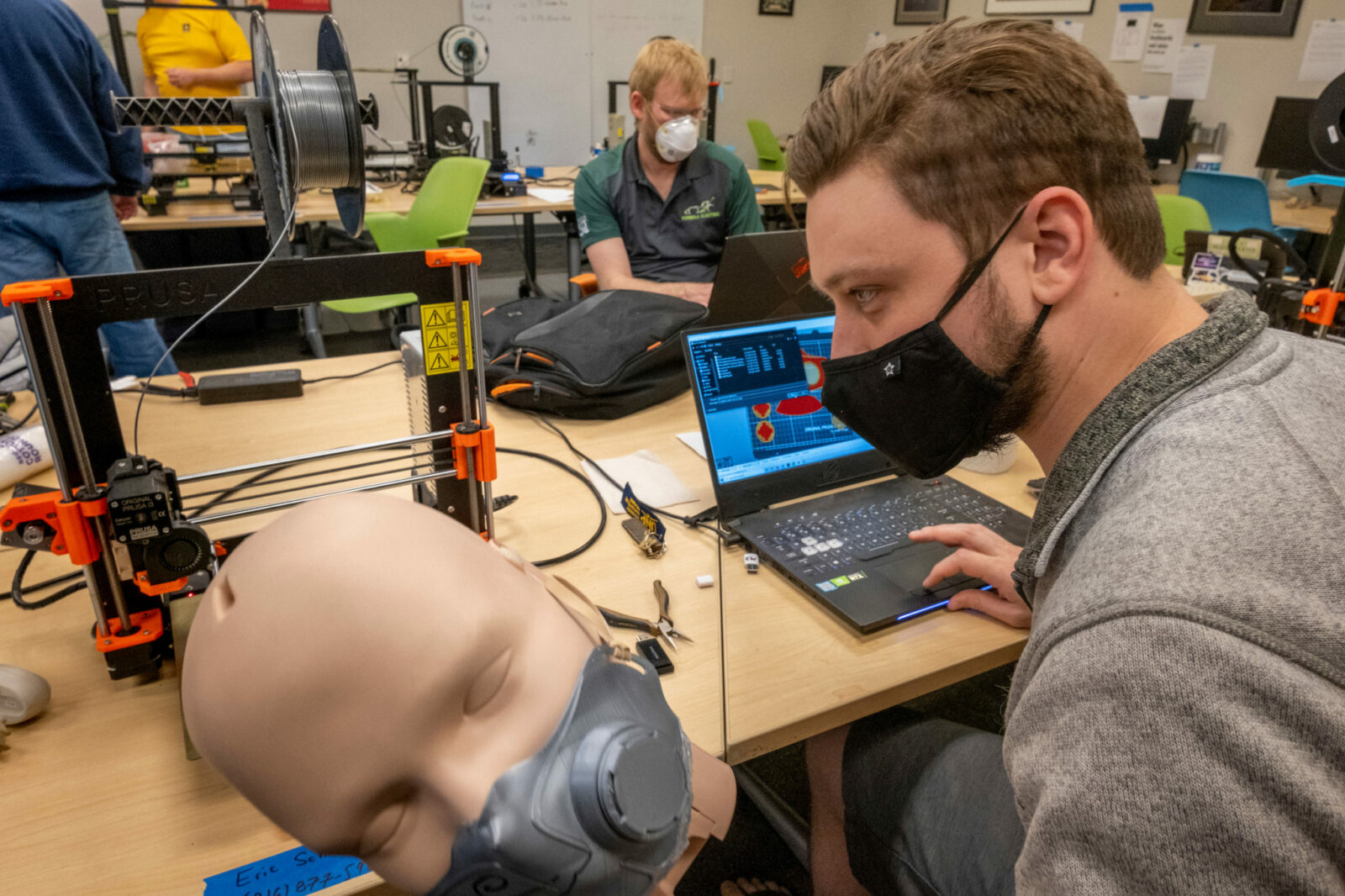 Eric Schneider, a senior aerospace engineering student at Missouri S&T, tests the fit of a prototype 3-D printed surgical mask on the head of a mannequin in the Kummer Student Design Center at S&T. In the background is Stephen Williams, an S&T mechanical engineering student. The university is helping Phelps Health prepare for coronavirus patients by 3-D printing masks and face shield brackets. Photo by Tom Wagner/Missouri S&T.