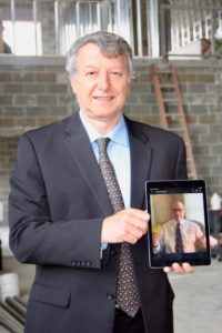 Dr. Khayat holding iPad photo of Dr. Poston giving a thumbs-up in a socially distanced award presentation