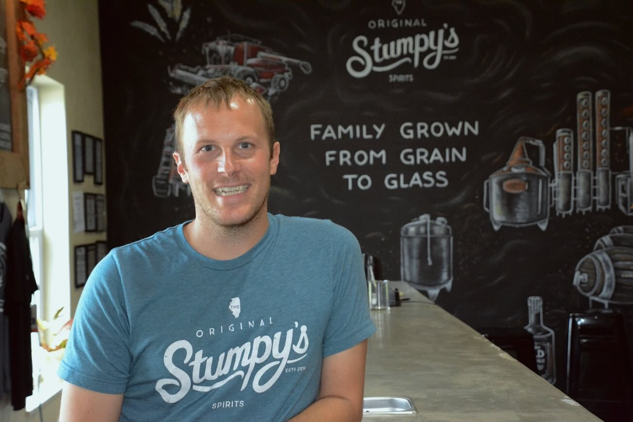 """Photo of Adam Stumpf in front of signs that reads, """"Family grown from grain to glass"""""""