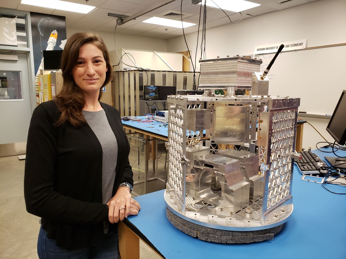 Jill Davis, Ph.D. student, in lab with small satellite