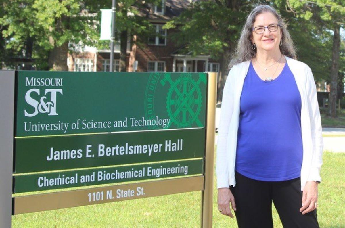 Photo of Dr. Christi Luks standing beside Bertelsemeyer Hall
