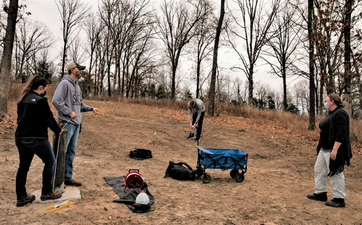 S&T students and their graduate teaching assistant working at groundwater monitoring well