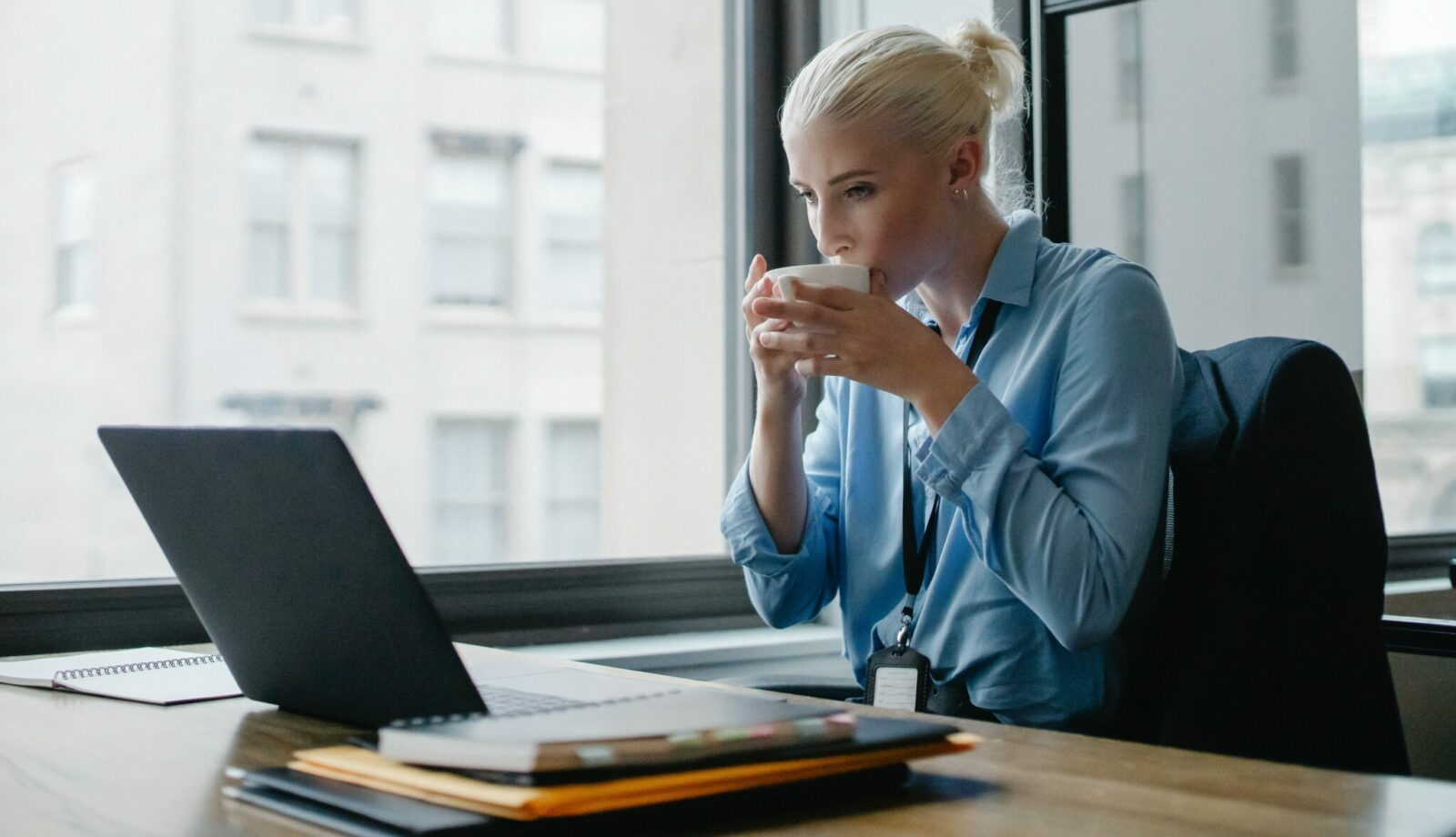 Photo of woman sipping a beverage at her computer