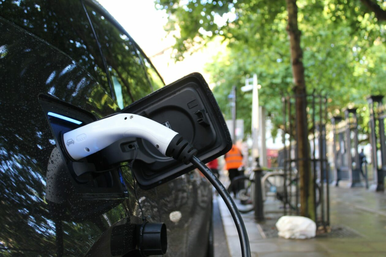 Photo of electric vehicle being charged on a tree-lined street