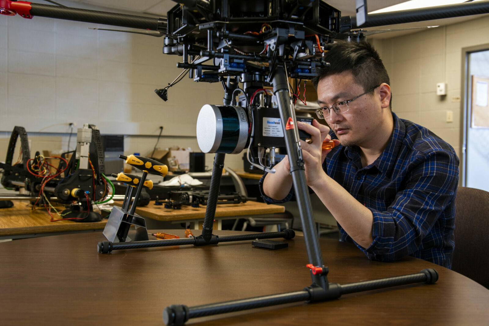 Photo of Xinzhe Yuan working on drone in lab