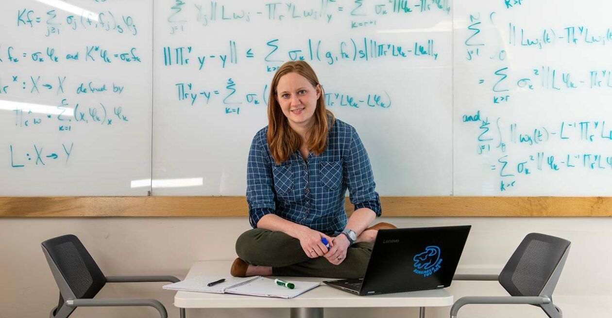 Student sitting on a table with a whiteboard behind her full of equations