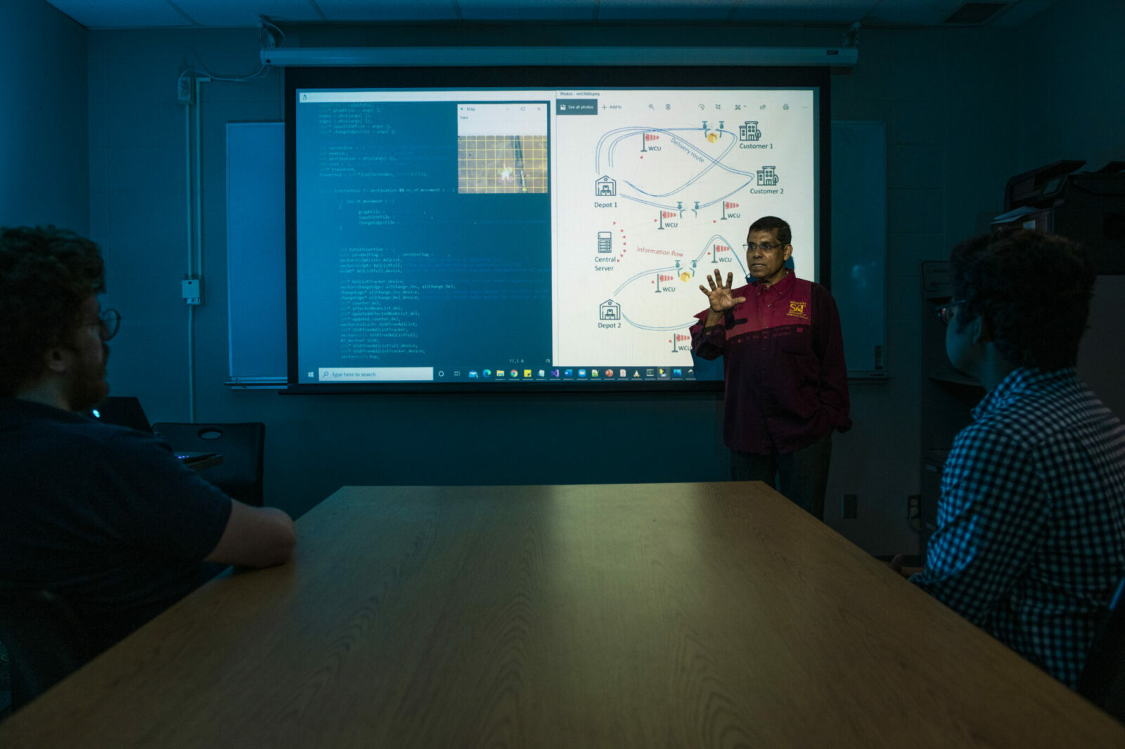 Photo of Dr. Sajal Das with projected image of CANDY project